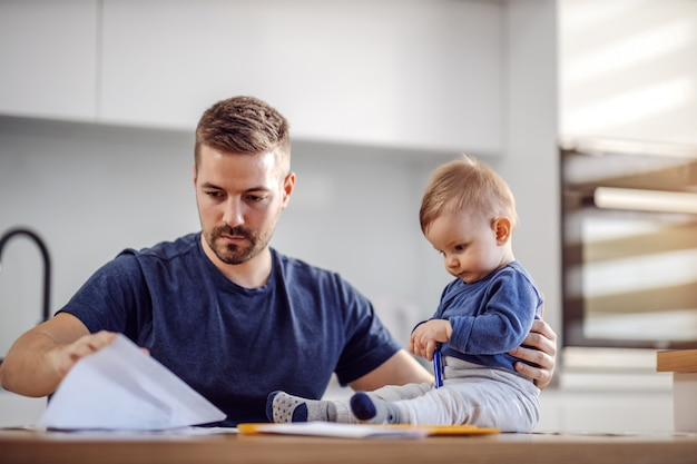 Jovem atraente barbudo pai sentado à mesa de jantar com seu amado filho adorável e pagando contas online. seu filho segurando uma caneta e tentando ajudá-lo.