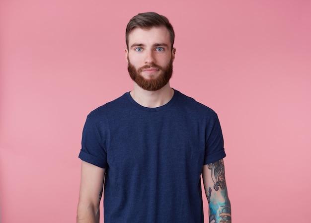 Jovem atraente barbudo ruivo, de olhos azuis, vestindo uma camiseta azul, olhando para a câmera com uma expressão facial calma isolada sobre um fundo rosa.