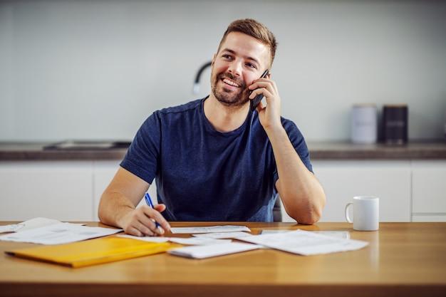 Jovem atraente barbudo sorridente homem chamando o atendimento ao cliente enquanto está sentado à mesa de jantar e preenchendo as contas.