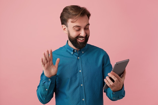 Jovem atraente barbudo vestido com uma camisa jeans, sorrindo, acenando com a mão, conversando com sua irmã no chat de vídeo. isolado sobre o fundo rosa.