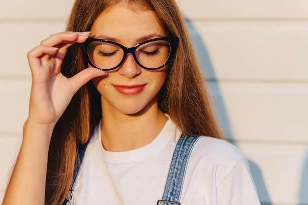 Jovem atraente bonita garota positiva em elegantes óculos no sol da manhã