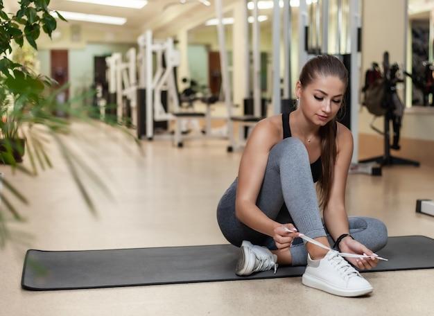 Jovem atraente cabe mulher amarrar cadarços de sapatos esportivos enquanto está sentado em uma esteira na academia