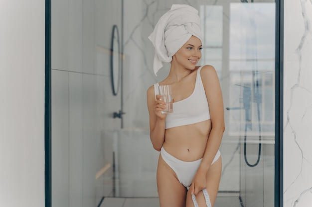 Jovem atraente cabe mulher em roupa íntima e com toalha de banho no cabelo molhado, segurando um copo de água mineral pura e fita métrica em pé no banheiro. estilo de vida saudável e conceito de perda de peso
