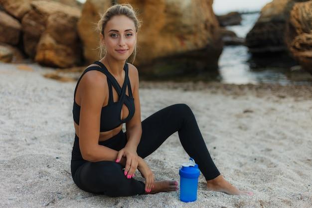 Jovem atraente cabe no sportswear está descansando após o treino enquanto está sentado na areia na praia selvagem.