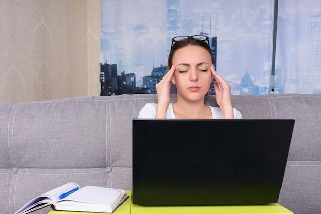Jovem atraente cansada fazendo uma massagem na cabeça enquanto trabalha em um laptop e faz seus negócios em casa, sentada em um sofá