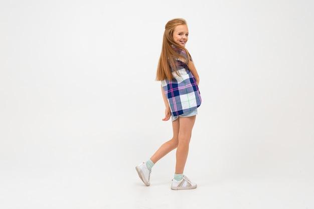 Jovem atraente caucasiana atraente em roupas casuais está de pé em pleno crescimento sobre um fundo azul claro estúdio