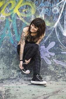 Jovem atraente caucasiana com tatuagens em pé contra uma rampa de patinação