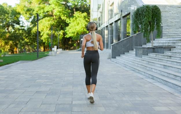 Jovem atraente caucasiana loira no sportswear fazendo corrida matinal enquanto ouve música em fones de ouvido, ao ar livre na cidade. treino matinal, estilo de vida saudável