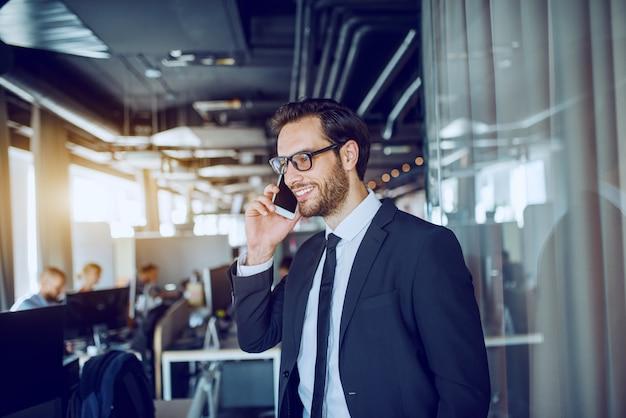 Jovem atraente caucasiano barbudo empresário sorridente de terno e óculos em frente ao seu escritório e tendo uma chamada comercial.