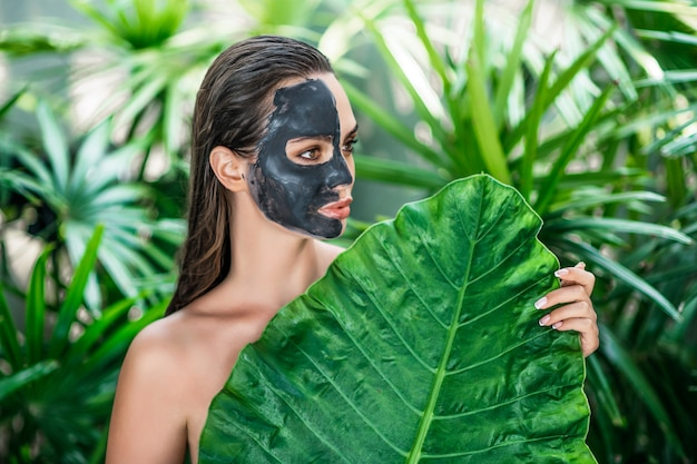 Jovem atraente colocou no rosto uma máscara de argila segurando uma folha verde