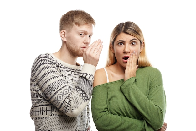 Jovem atraente com a barba por fazer compartilhando segredos ou sussurrando fofocas no ouvido de sua namorada surpresa, que está olhando com a boca aberta, chocada com informações inesperadas