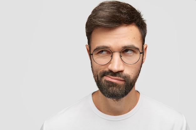 Jovem atraente com a barba por fazer parece duvidoso, pensativamente de lado, franze os lábios, tem uma barba espessa e escura
