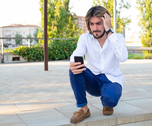 Jovem atraente com barba, camisa branca olha para o seu smartphone preocupado no parque.