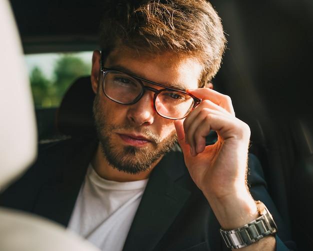 Jovem atraente com barba e óculos com cara séria olha para a câmera. homem de negocios.