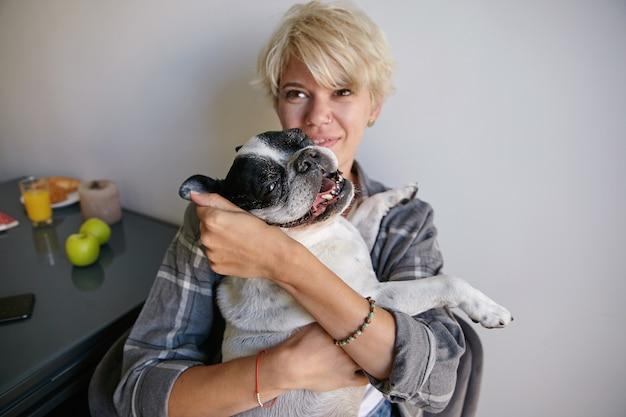Jovem atraente com cabelo loiro curto segurando e abraçando seu cachorro adulto, animal de estimação parece satisfeito e feliz, posando no interior da casa
