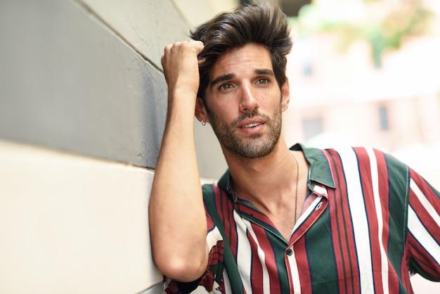 Jovem atraente, com cabelos escuros e penteado moderno, vestindo roupas casuais ao ar livre
