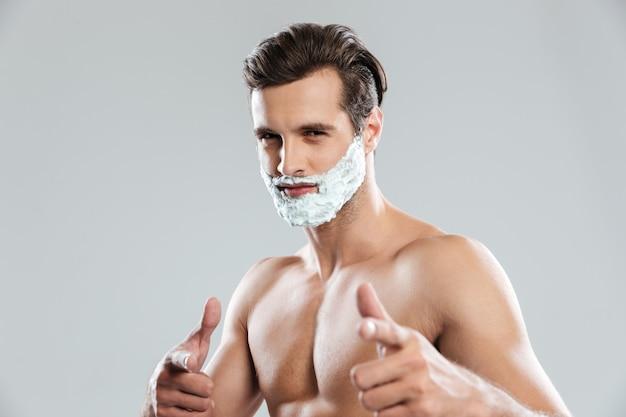 Jovem atraente com espuma de barbear no rosto apontando