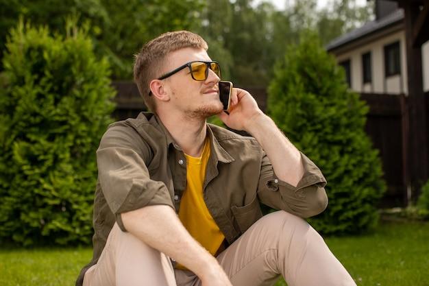 Jovem atraente com roupas casuais olhando para longe e falando no celular enquanto está sentado sozinho na grama, férias de verão, fim de semana, tarifas para operadora de chamadas móveis, conceito de celular