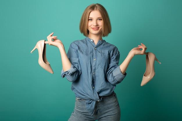 Jovem atraente com sapatos nas mãos
