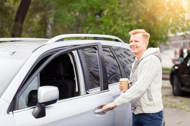 Jovem atraente com um copo de papel de café no carro