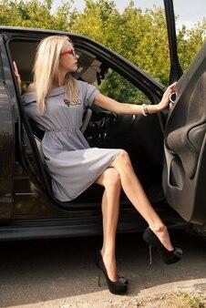 Jovem atraente com um vestido listrado de óculos e sapatos de salto alto sentada no carro abrindo a porta