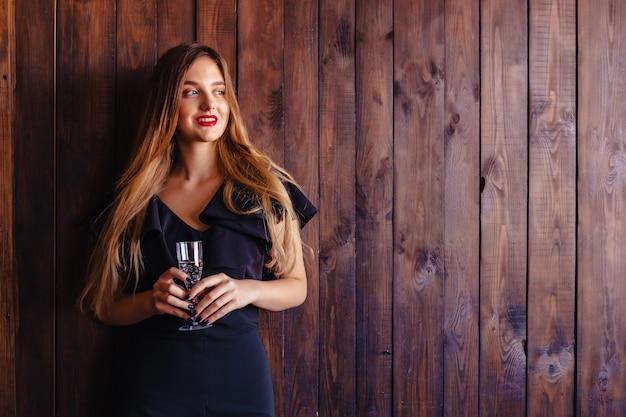 Jovem atraente com uma taça de champanhe ou vinho no fundo da parede
