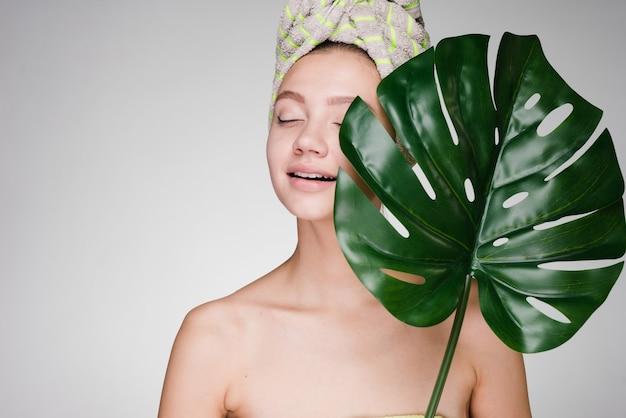 Jovem atraente com uma toalha na cabeça segurando uma folha verde, desfrutando de um spa