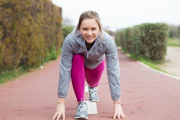 Jovem atraente conteúda pronta para corrida ao ar livre