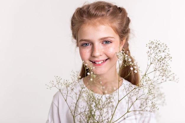 Jovem atraente. criança simpática e bonita, feliz ao carregar flores do campo e sorrindo com dentes fortes