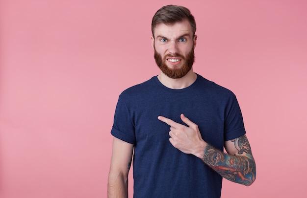 Jovem atraente de barba vermelha com olhos azuis parece indignado, vestindo uma camiseta azul, franzindo a testa com nojo, apontando o dedo para o espaço da cópia no lado esquerdo isolado sobre fundo rosa.