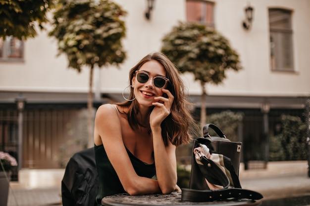 Jovem atraente de cabelos escuros com lábios vermelhos, óculos de sol modernos e vestido de seda, sorrindo e posando ao ar livre