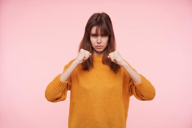 Jovem atraente de cabelos escuros semicerrando os olhos enquanto olha de forma ameaçadora, mantendo os punhos erguidos enquanto posa sobre a parede rosa