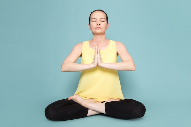 Jovem atraente de camisa amarela e calça preta, fazendo posturas de ioga