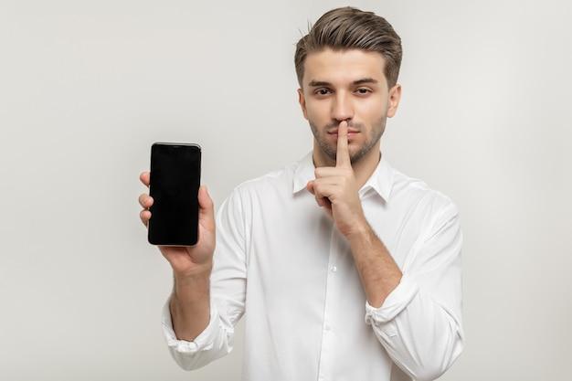 Jovem atraente de camisa branca segurando um celular fazendo um gesto silencioso