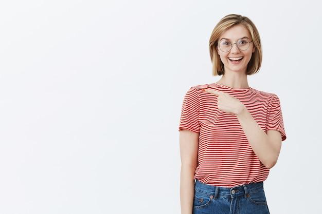 Jovem atraente de óculos mostrando seu caminho, apontando o dedo esquerdo para copyspace