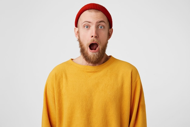 Jovem atraente de olhos azuis e barba parece surpreso