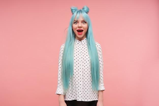 Jovem atraente, de olhos bem abertos, com longos cabelos azuis olhando espantada e mantendo a boca bem aberta, vestida com uma camisa com pontos pretos em pé