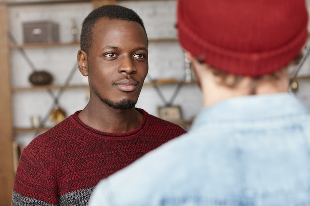 Jovem atraente de pele escura, suéter casual, conversando com seu amigo irreconhecível que ele encontrou no café, ouvindo-o com um olhar interessado e feliz. dois homens conversando dentro de casa