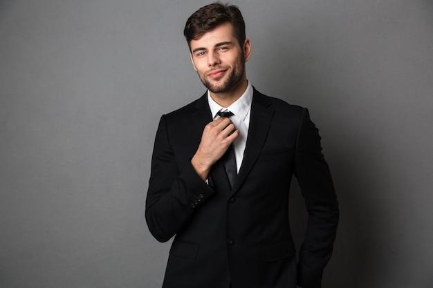 Jovem atraente de terno clássico ajeita a gravata dele,