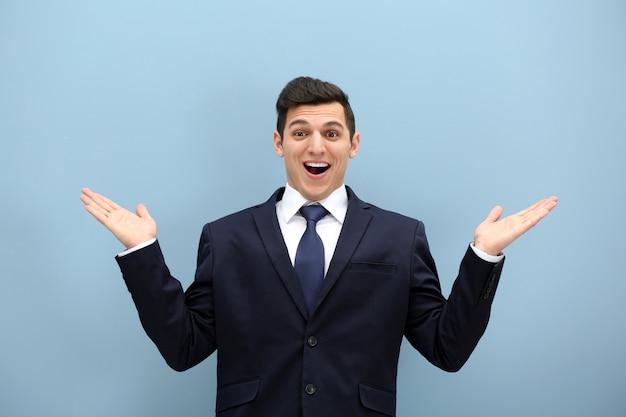 Jovem atraente de terno contra uma parede azul clara
