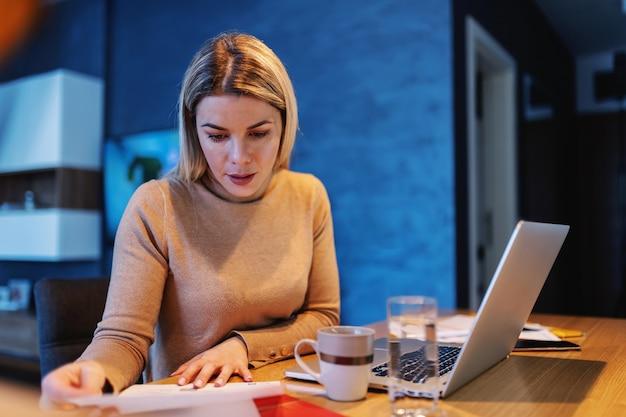 Jovem atraente dedicada ocupada empreendedora olhando para a papelada enquanto está sentado em casa durante o surto de coronavírus.
