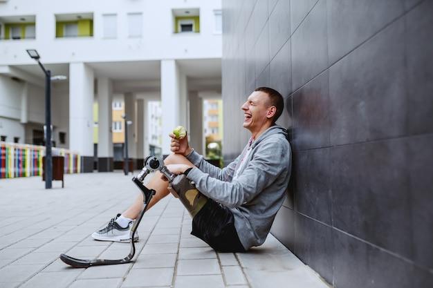 Jovem atraente desportista caucasiano com perna artificial, sentado no chão, encostado na parede e comendo maçã fresca.