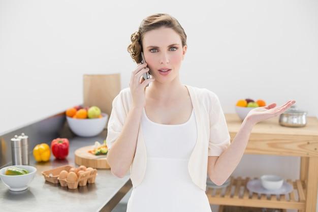 Jovem atraente discutindo no telefone em pé na cozinha