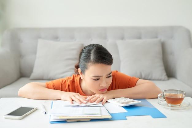 Jovem atraente dona de casa chateada com contas de luz, faz a conta do orçamento familiar e paga as contas online, estando em casa