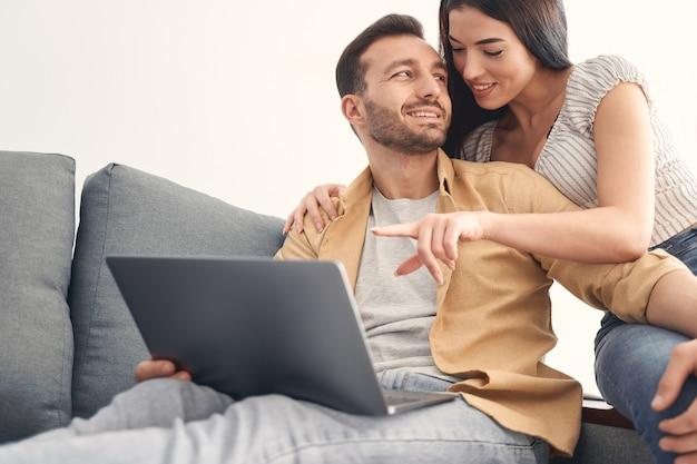 Jovem atraente e adorável homem e mulher passando momentos de lazer juntos e sentados no sofá enquanto usam o laptop