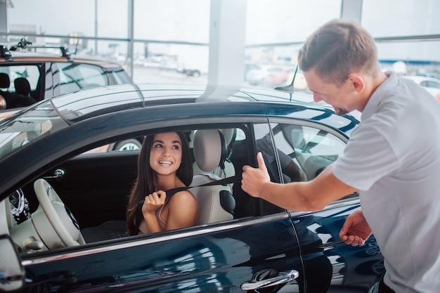 Jovem atraente e alegre senta-se no carro. ela olha para o consultor e sorri para ele. o homem segura a porta com uma mão e sorri também.