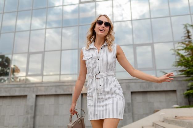 Jovem atraente e elegante mulher com cabelo loiro andando nas ruas da cidade com vestido branco de estilo de moda de verão usando óculos escuros