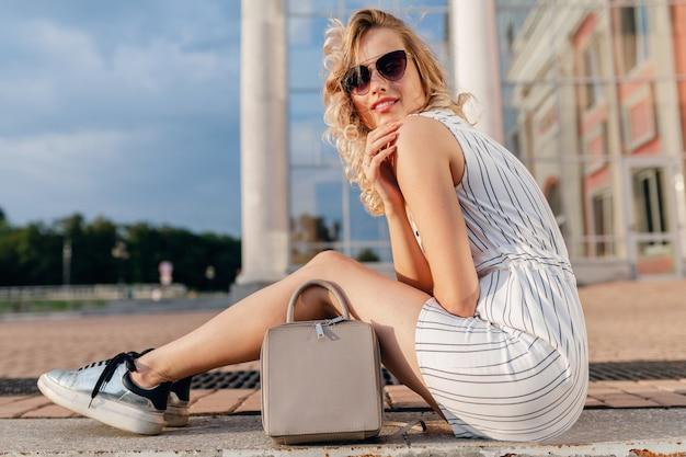 Jovem atraente e elegante mulher loira sentada na rua da cidade, com vestido de estilo de moda de verão, usando óculos escuros, bolsa e tênis prateados
