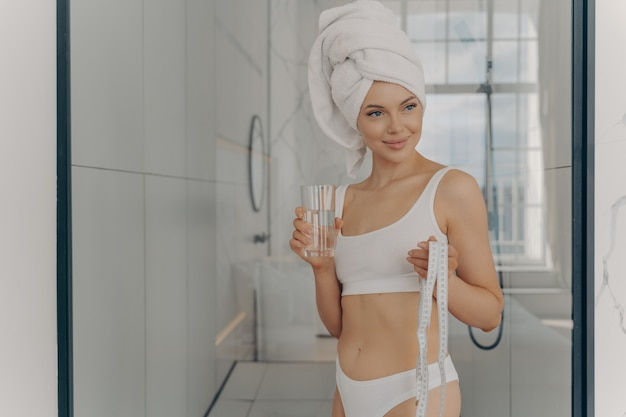 Jovem atraente e esportiva saiu do chuveiro com uma toalha na cabeça, segurando a fita métrica e se refrescando com um copo de água mineral depois de fazer ioga em casa. conceito de estilo de vida saudável