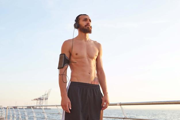 Jovem atraente e esportivo barbudo após esportes radicais à beira-mar, descansar depois de correr, olhando para o mar e ouvindo músicas em fones de ouvido,